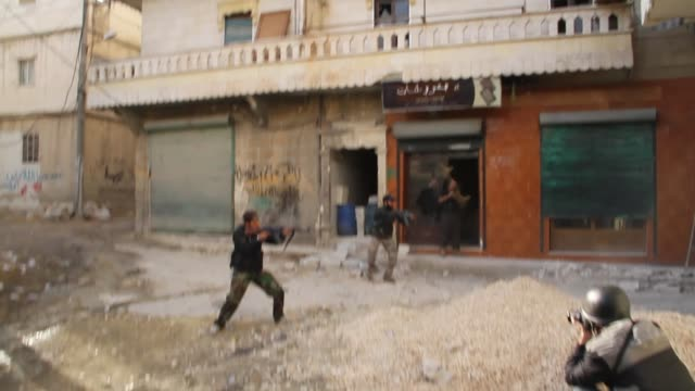 Free Syrian Army fighters fire weapons at the frontline in Aleppo Syria