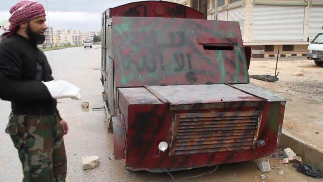 Free Syrian Army fighters inspect a armored vehicle or homemade tank in Aleppo Syria / It was used to rescue injured people and avoid sniper fire
