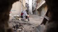 Free Syrian Army Fighters yell at women and children who are in the line of fire at the frontline in Aleppo Syria