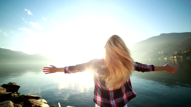 Freedom-Woman arms outstretched by the lake