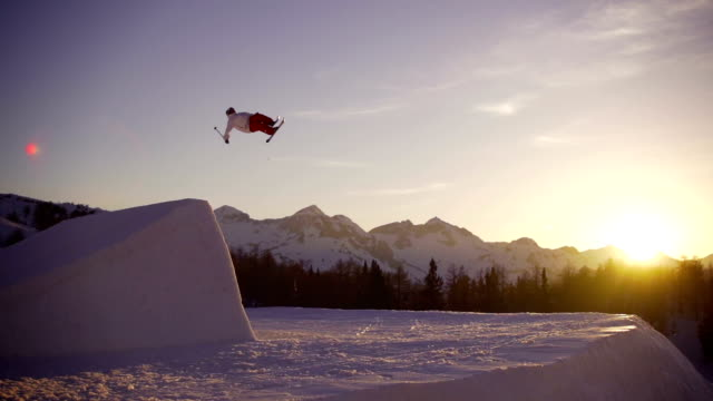 Freestyle skier performing a trick at sunset
