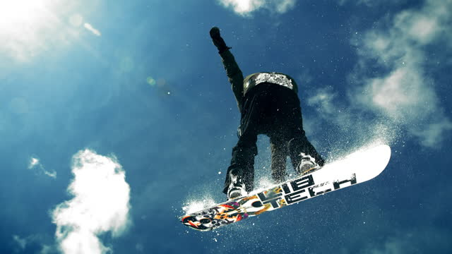 SLO MO TD Freestyle snowboarder flying off and rotating