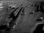Freight cars in train yard INT Harry Carpenter sitting at freight desk filling out destination tags '4' '5' handing them off to male