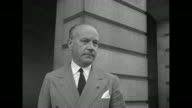 French Ambassador to the US Gaston HenryHaye climbing steps to State Department building followed by another man / he stands at top of steps for...