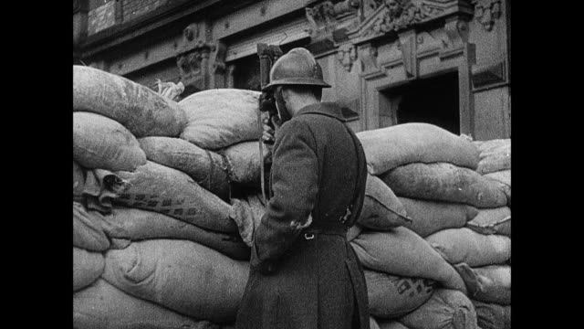 MONTAGE French Army soldier manning guard post behind sandbags, damaged buildings in town, and soldier in a bunker playing xylophone / Strasbourg, France
