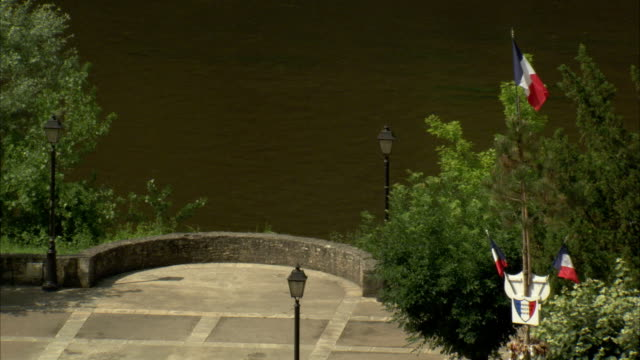 French flags wave on a riverbank. Available in HD
