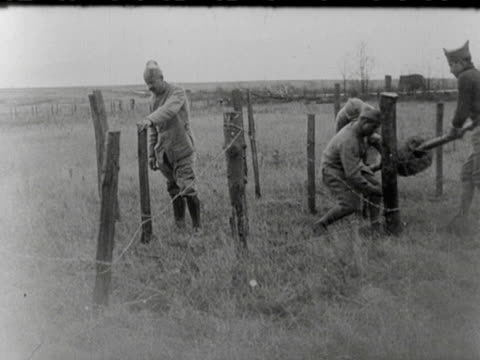 / French infantry trekking along a muddy road / soldiers look happy and greet the camera / French soldiers installing a barricade of barbed wire in...