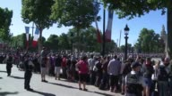 French nationals and tourists watch the annual military parade on the Champs Elysee marked this year by the attendance of US President Donald Trump...