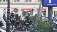 French parisian firefighters on duty in front of a church and near then inside a parking lot