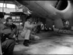 MILITARY French soldiers in hangar w/ American USAF officer under parked Lockheed T33 'Shooting Star' jet trainer aircraft men watching landing gear...