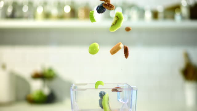 SLO MO fresh and dried fruit flying into a mixer