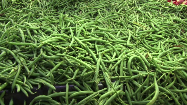 Fresh green beans fill a huge bin at a market.