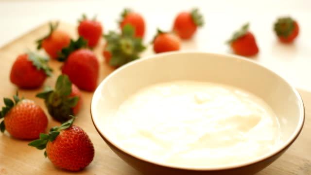 Fresh strawberries splashing into yogurt