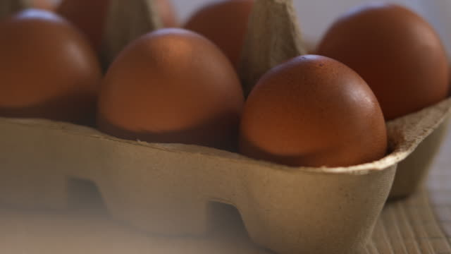 Freshly laid organic brown hen eggs in recyclable brown cardboard egg tray on wooden farm table