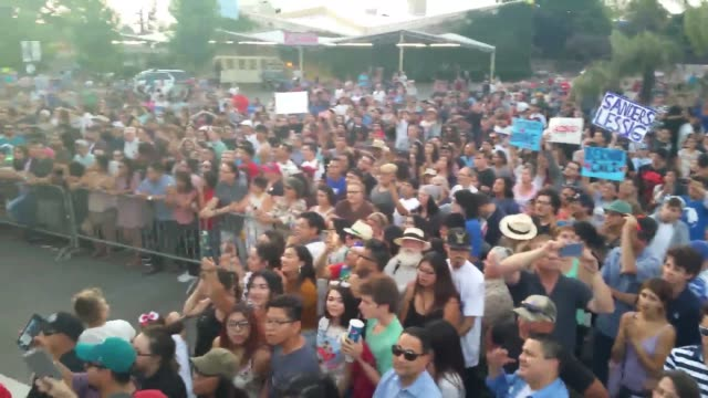 Footage of Bernie Sanders speaking to his supporters and of his supporters listening to him speak at his rally in Fresno