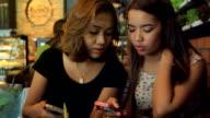 Friend looking at Digital Tablet in Coffee Shop