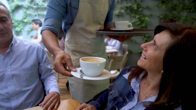Vriendelijke zwarte ober serveren koffie naar een groep mensen aan een tafel