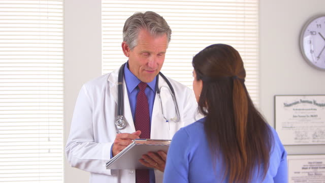 Friendly doctor asking elderly patient some questions