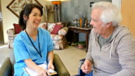 Friendly home healthcare nurse examining senior male patient in assisted living facility