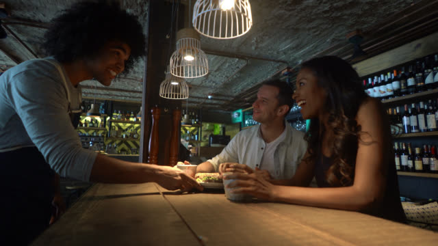 Friendly waiter serving a sandwich to a multi ethnic couple on a date