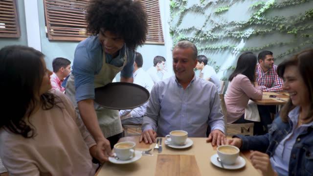 Vriendelijke ober serveren van koffie aan een groep van volwassenen op zoek zeer tevreden