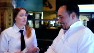 Friendly waitress being trained by Hispanic chef in casual restaurant