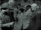 Friends and admirers of occupying German invaders standing along street waving and offering fascist Nazi salute / Polish betrayers loyalists and...