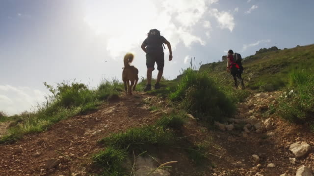 Friends and dog hiking in Italian Apennines mountains