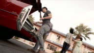 Friends arriving at Vegas motel in classic convertible unload trunk and carry luggage upstairs to room