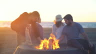 Friends building a campfire on the beach
