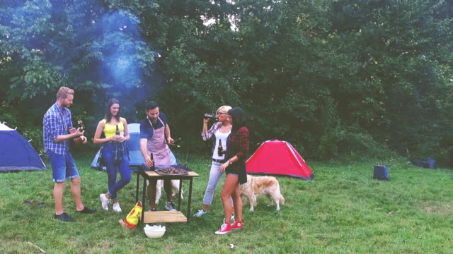 Friends camping and having a barbecue in forest