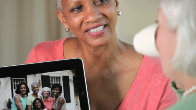 CU TU TD Friends discussing family portraits on tablet computer / Richmond, Virginia, United States