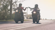 SLO MO. Friends driving motorcycles side by side join hands in greeting and speed up on two land road.