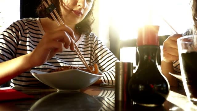 Vrienden eten van noedels op de eettafel