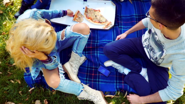 Friends eating pizza on picnic