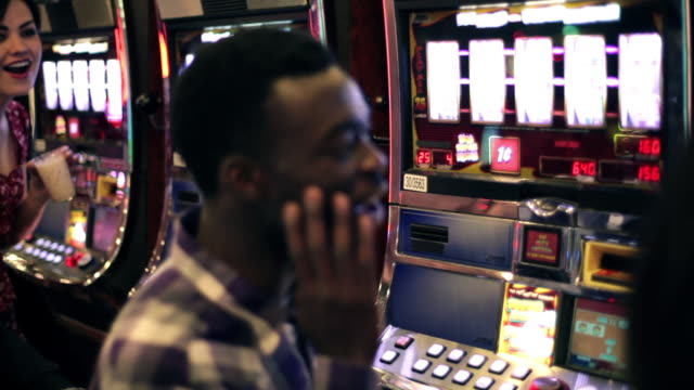 Friends freak out and cheers drinks as young woman wins at slots in Vegas casino