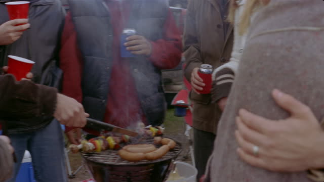 Friends grilling hot dogs and shish kebabs and drinking beers at tailgate party on chilly day