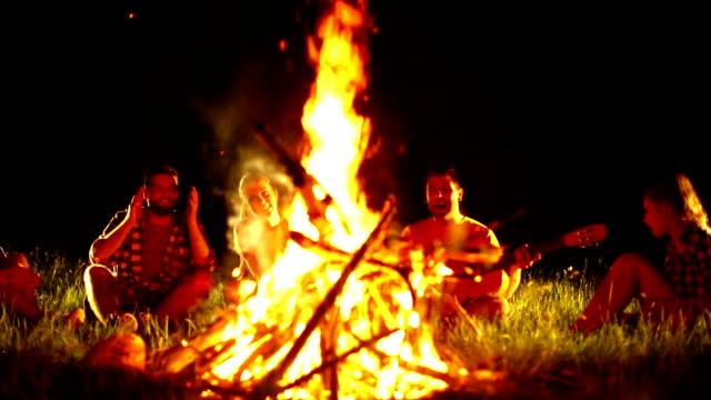 Friends having fun by campfire.