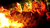 Friends having fun by campfire.