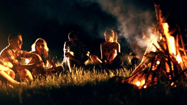 Vrienden plezier door kampvuur.