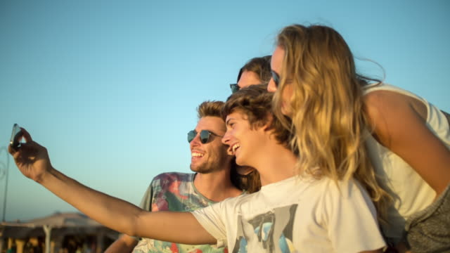 4 friends in parking off-road car nearby a beach during sunset - having great fun and taking selfies