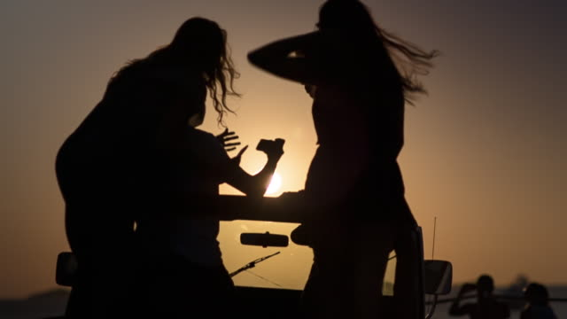 4 friends in parking off-road car nearby a beach during sunset - having great fun and taking selfies - silhouette shot