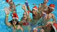 SLO MO Friends in the pool waving into the camera while holding their drinks and wearing Santa hats