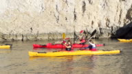 Friends kayaking along rocky coast