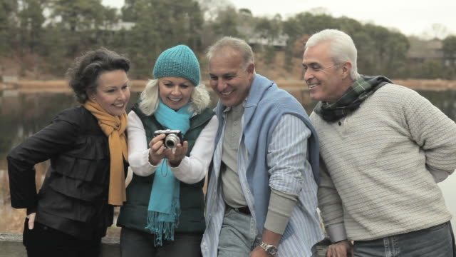 Friends looking at digital camera and laughing