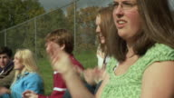 CU Friends (12-17) on bleachers, cheering, Cazenovia, New York, USA
