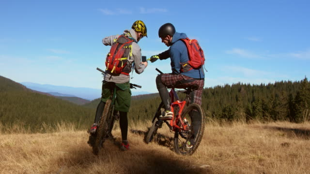 Friends on mountain bikes searching for the right trail with a phone