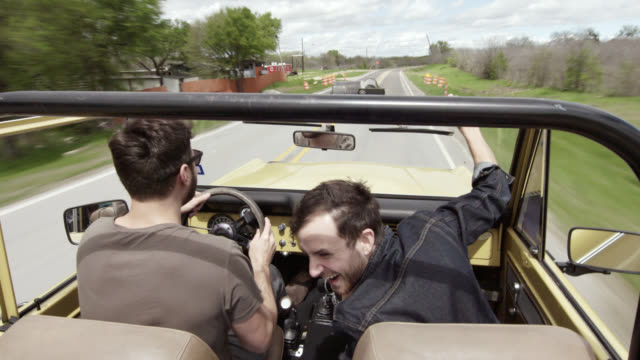 Friends on road trip cruise in classic Bronco, laugh and cheer