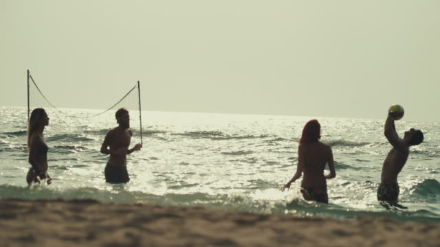 Friends play beach volley in the sea