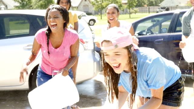 Vänner hälla hink med vatten över flickans huvud på biltvätt